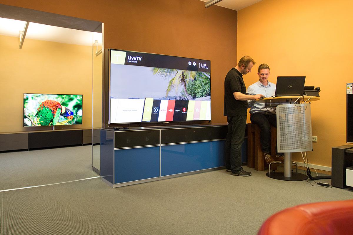 Unsere Mitarbeiter Robert und Stefan. Im Hintergrund ein LG TV mit der neuen webOS Oberfläche.